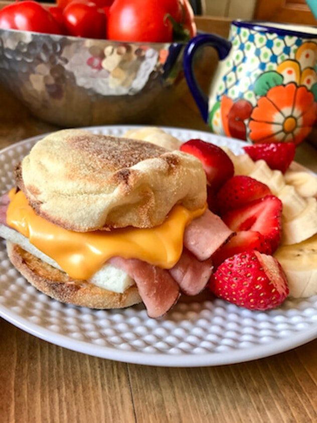 english muffin with egg, ham and cheese next to sliced strawberries and bananas on a white plate