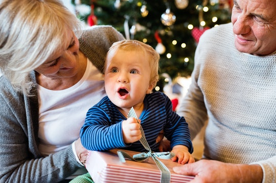grandparents sitting with baby on their lap, opening a christmas present