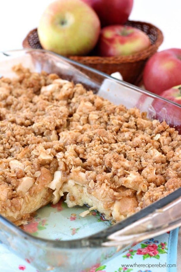 glass pan of apple crisp french toast with slice missing and apples in the background