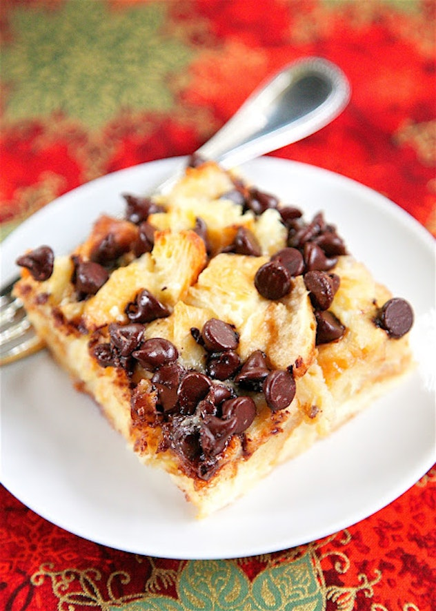 slice of croissant baked and cut into square with melted chocolate chips on top on white plate situa...