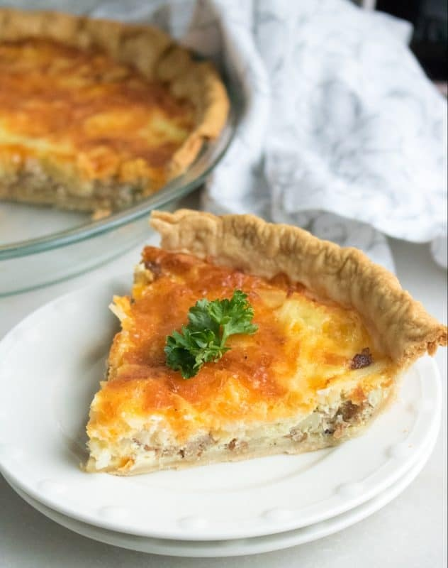 slice of quiche on white plate with remaining quiche in the background
