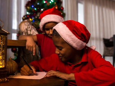 kid wearing santa hat, writing his wishlist to santa
