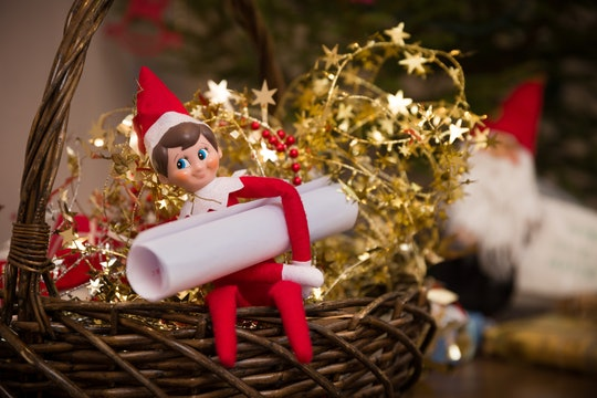 elf on the shelf doll in a basket with gold star garland and a letter