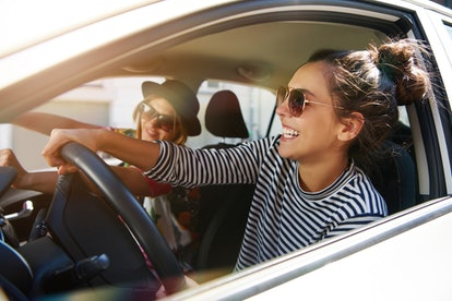 Happy young women in car, having the best week of June 7, 2021, per their zodiac signs.