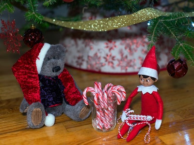an elf on the shelf doll in front of a Christmas tree with candy canes
