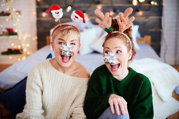 Two girls laugh in their bedroom dressed festive for Christmas, while one wears reindeer antlers and the other wears Santa ears.