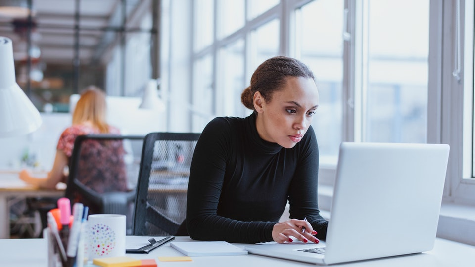 woman in black turtle neck intently staring at laptop at desk in office