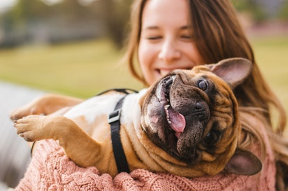 A woman holds her dog who is smiling with his tongue out.