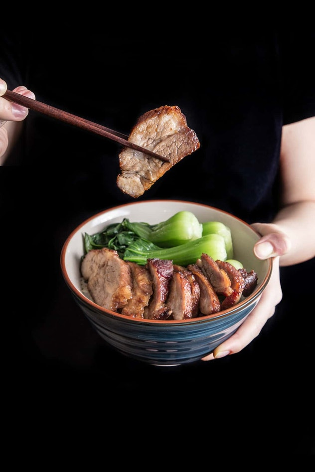 close up of someone holding up bowl and slice of pork with chopsticks