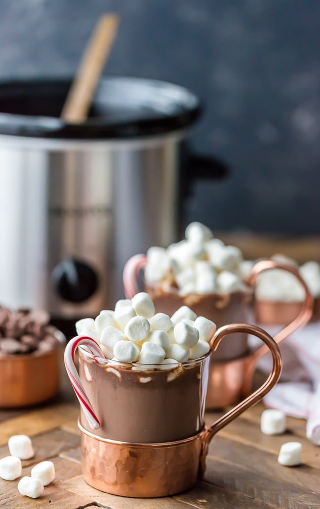 copper and glass mugs of hot chocolate with marshmallows on top and a candy cane hanging off the left side