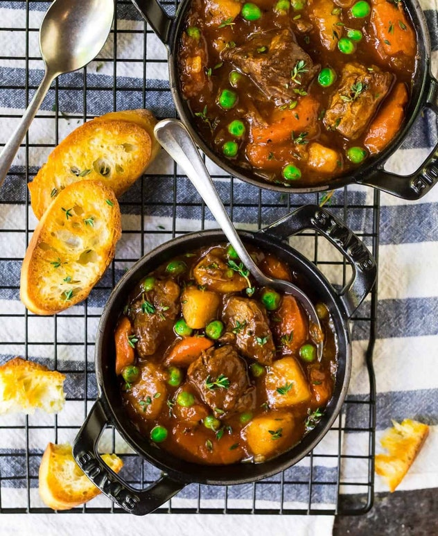 aerial view of two pots of beef stew with potatoes, peas, and carrots on cooling rack. slices of toasted bread arranged around the bowls.