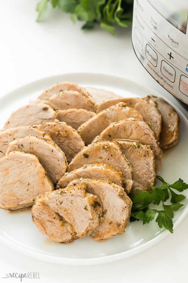 plate of sliced pork tenderloin next to pressure cooker