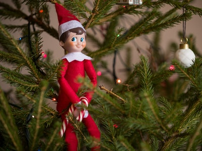 and elf on the shelf perched in a Christmas tree