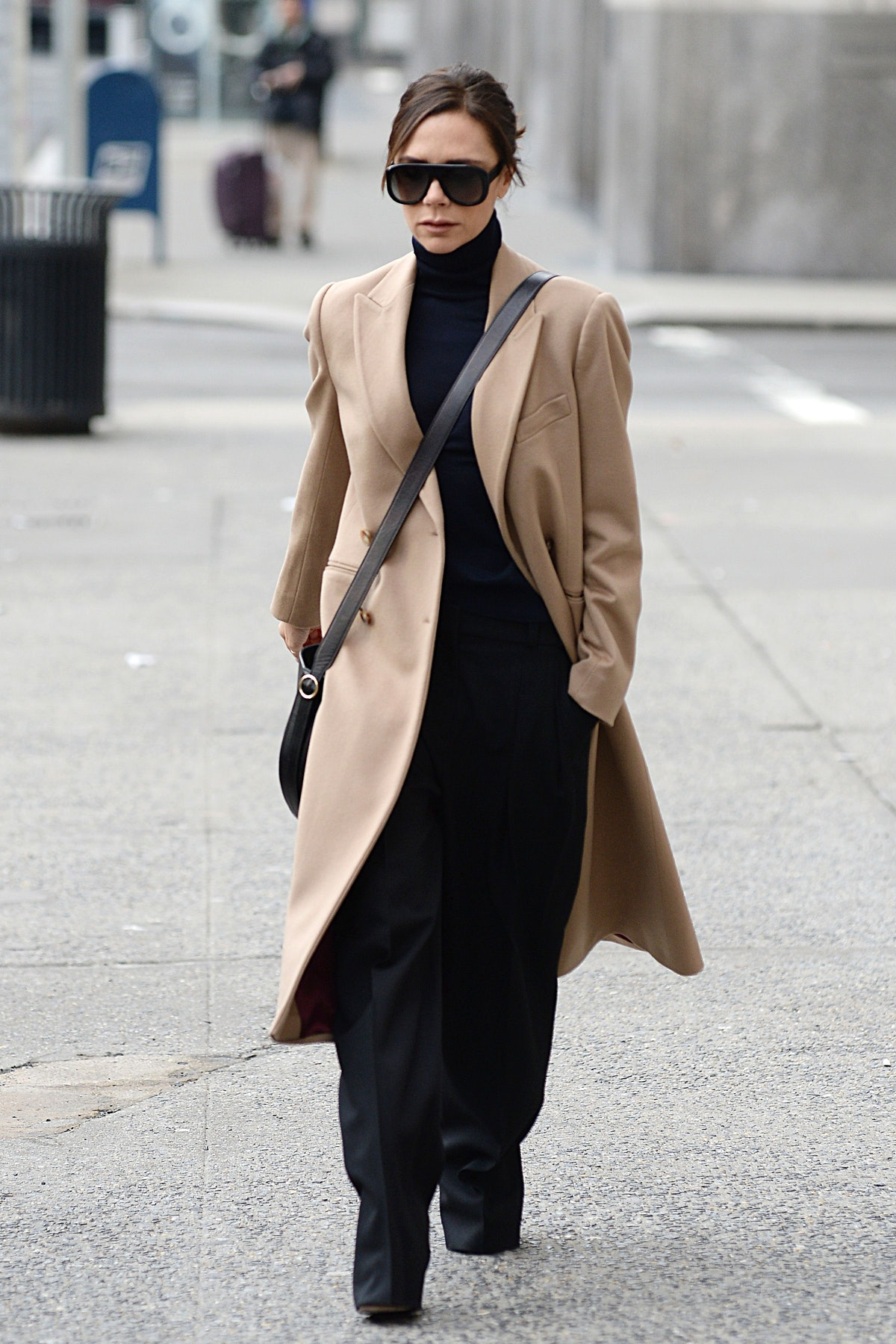 Victoria Beckham wearing a camel coat, black sunglasses, a turtleneck, and trousers.