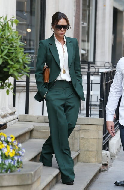Victoria Beckham wearing a green two-piece suit.
