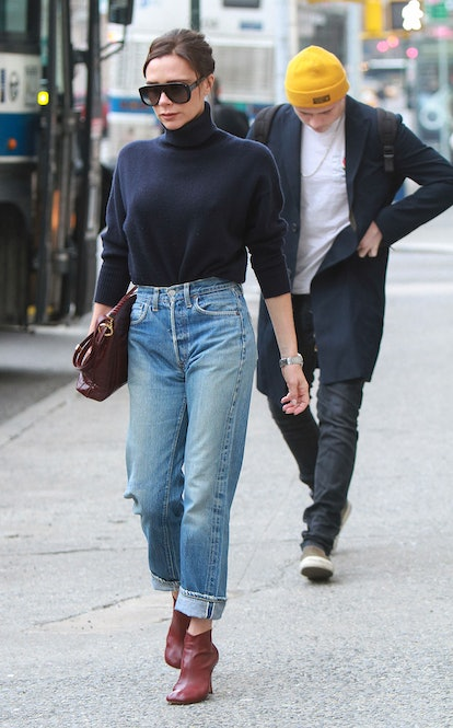 Victoria Beckham wearing high-waisted jeans and a turtleneck.