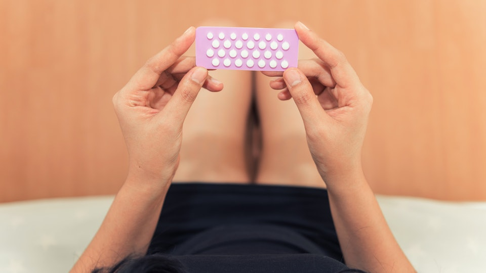 woman's hands holding birth control pills