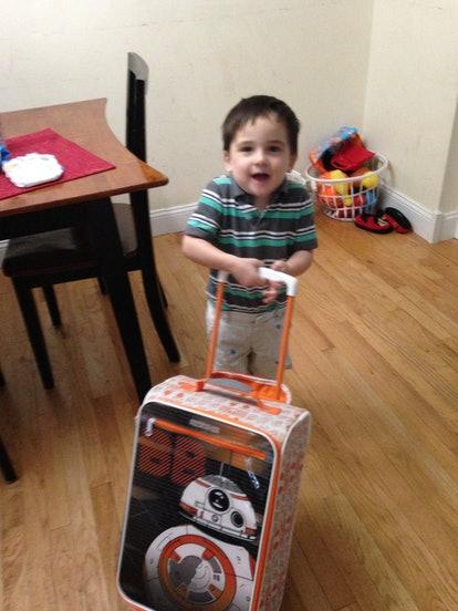 A young child pulls a wheelie suitcase