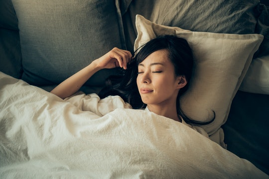 symbols in dreams that can predict you're pregnant; a woman sleeping in bed, dreaming