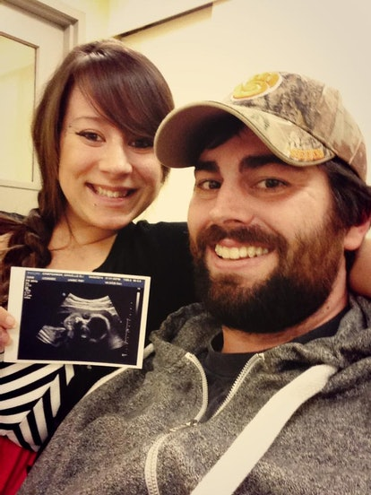 A picture of the author, smiling, with her partner as she holds up an ultrasound picture.