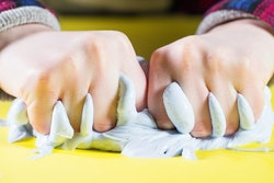 closeup of kid's hands squeezing slime