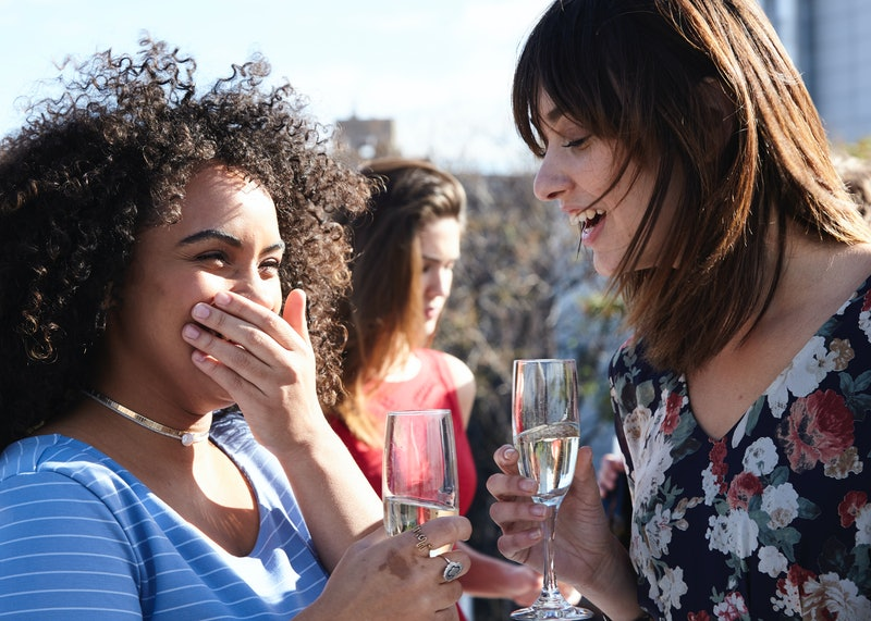 Two women share drinks on a rooftop. Doctors explain subtle symptoms of alcohol intolerance.