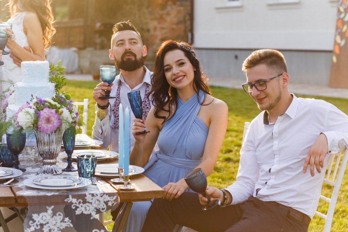 A happy couple holds up their glasses to cheers to the happy couple at a wedding outdoors.