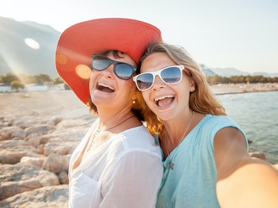 mom and daughter taking mother's day selfie outside