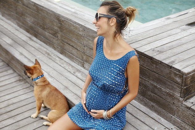 woman in blue dress and sunglasses smiling siting on wooden bench near pool and light brown dog, holding belly