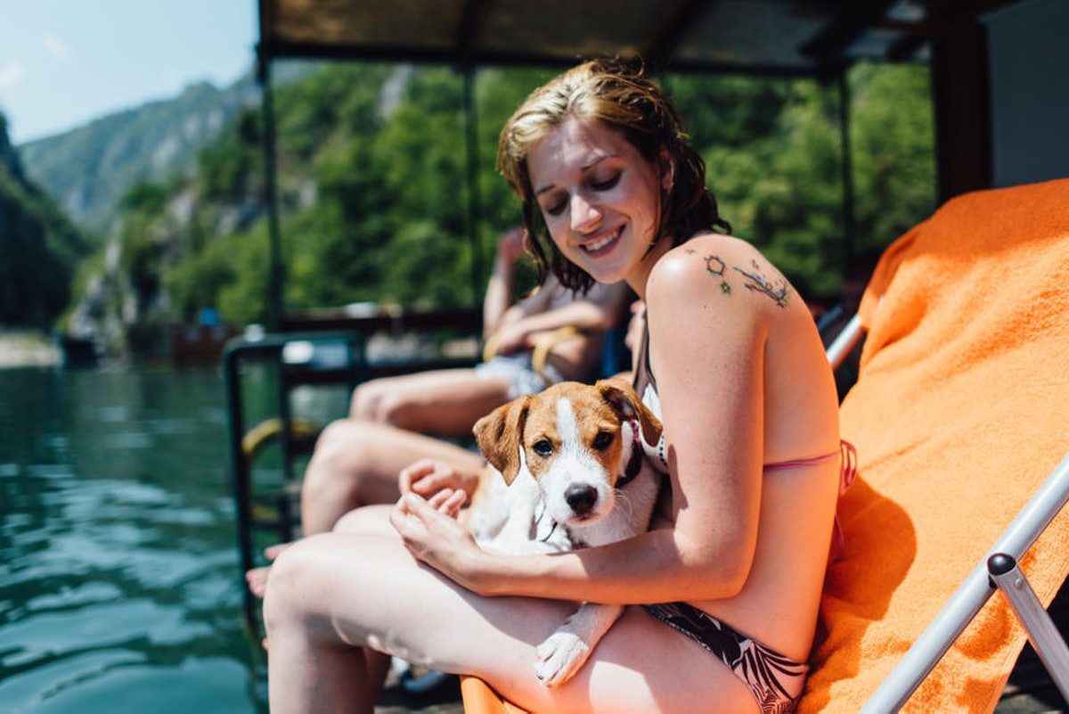 Young woman holding her dog at her friend's lake house, in need of lake Instagram captions.
