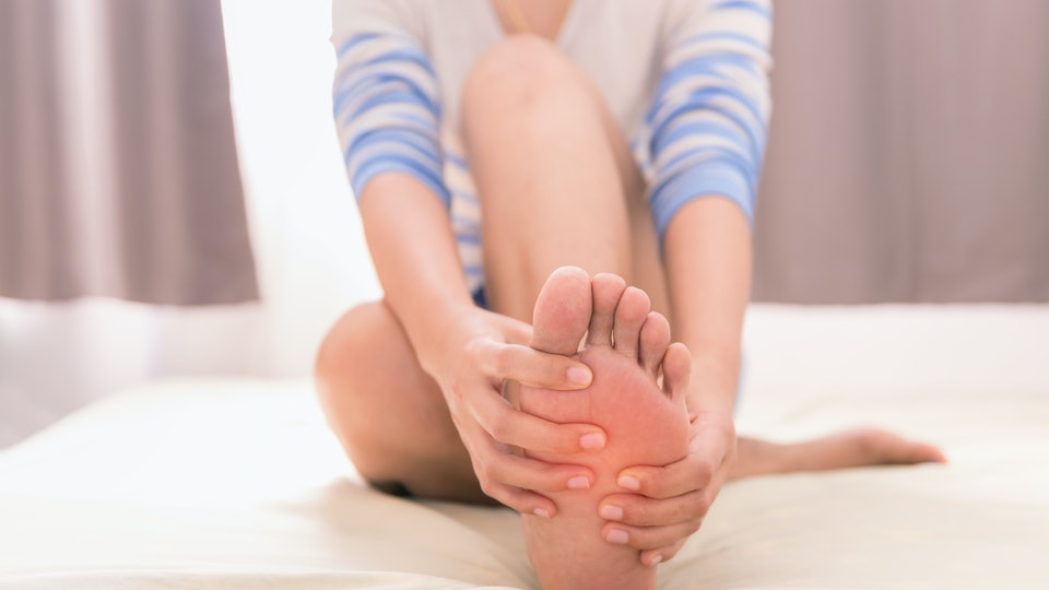woman on white bed massaging her foot