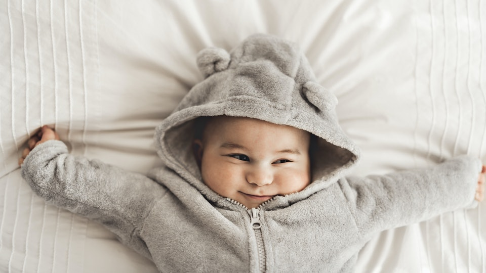 cute baby with chubby cheeks smiling on back with arms wide open in a fuzzy grey onesie with a hood
