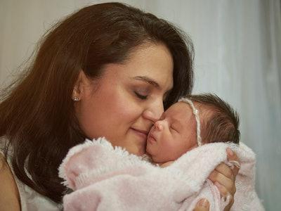brunette woman holding baby pressing lips against newborns cheek