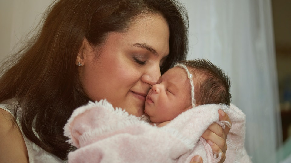 brunette woman holding baby pressing lips against newborns cheek