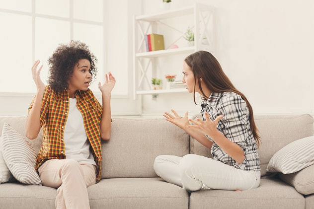 two women with their hands up fighting on couch