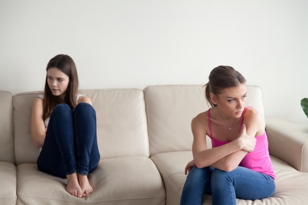 two women on couch looking away from each other angry