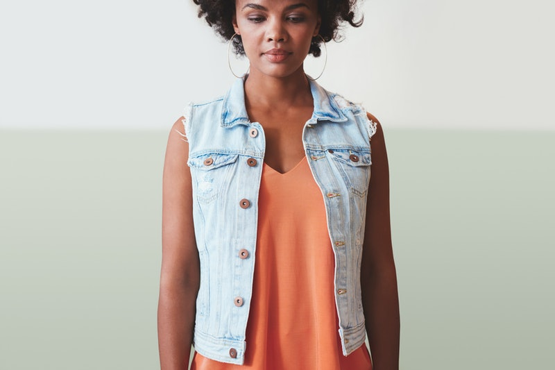 A woman wearing an orange dress and denim vest looks down, wondering how long it will take to get over her ex