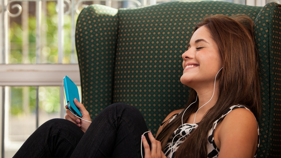 woman eyes closed smiling on chair listening to music from phone