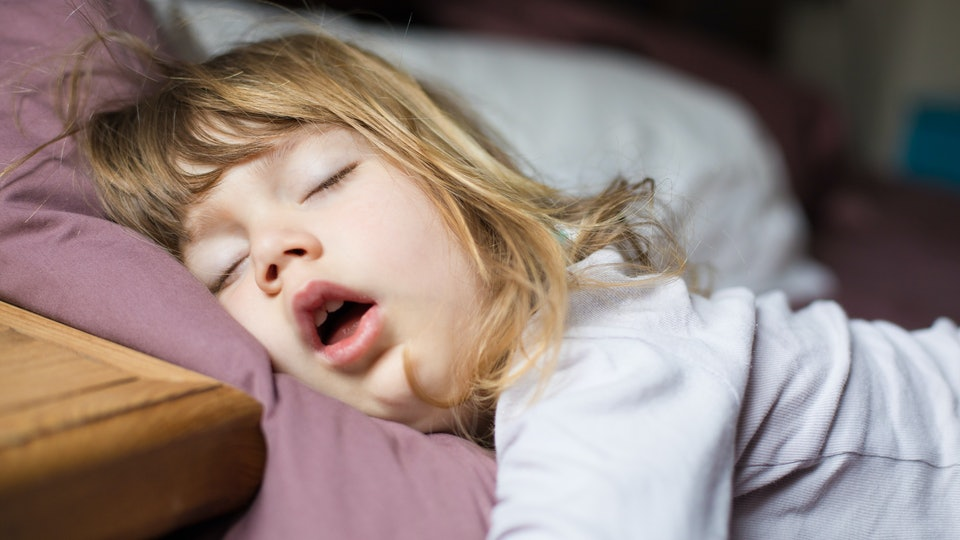 Experts weigh in on when it's safe for a toddler to sleep with a pillow.
