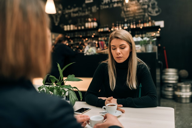 Two women talking over coffee. One woman looks at the table, clearly upset.