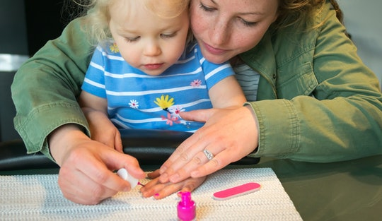 Mother helping young child paint nails pink