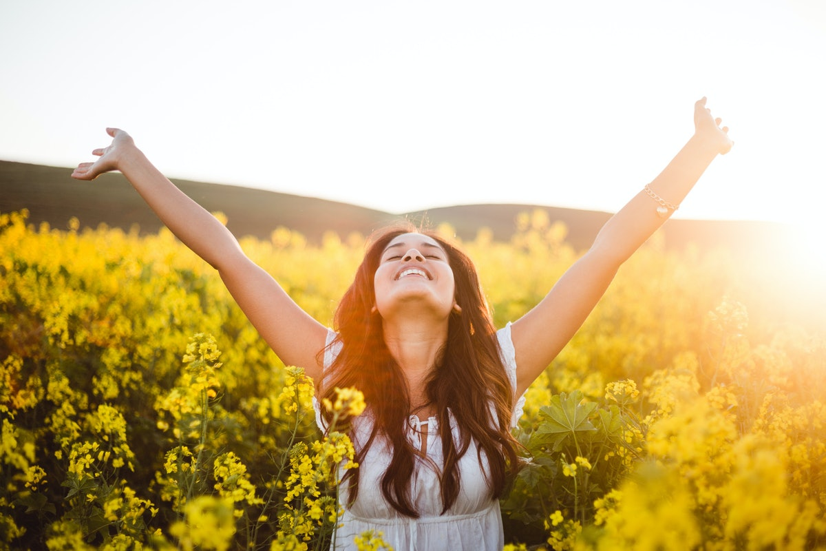 Young woman throwing her hands up in a flower field before posting flower captions on Instagram.