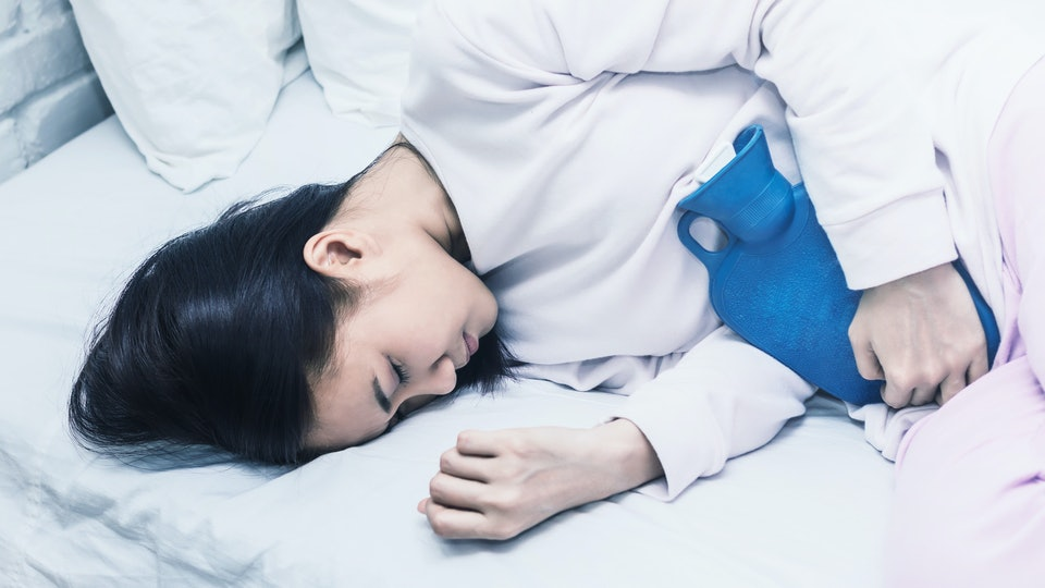 woman laying on side in white bed with blue hot water bottle held against her stomach