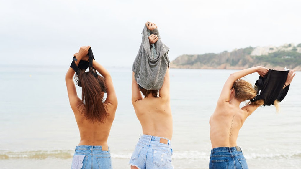 Three women in jean shorts by the ocean.