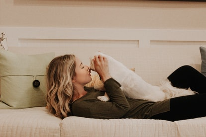 The writer snuggles her dog on a daybed. Having companionship is an important part of coping with a BRCA positive diagnosis.