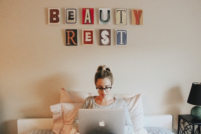 """The writer sits in front of a wall hanging saying """"Beaty rest."""" Self-care is an important component ..."""