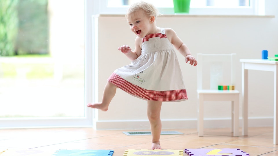 toddler in white and red dress stomping and dancing on foam tiles laughing