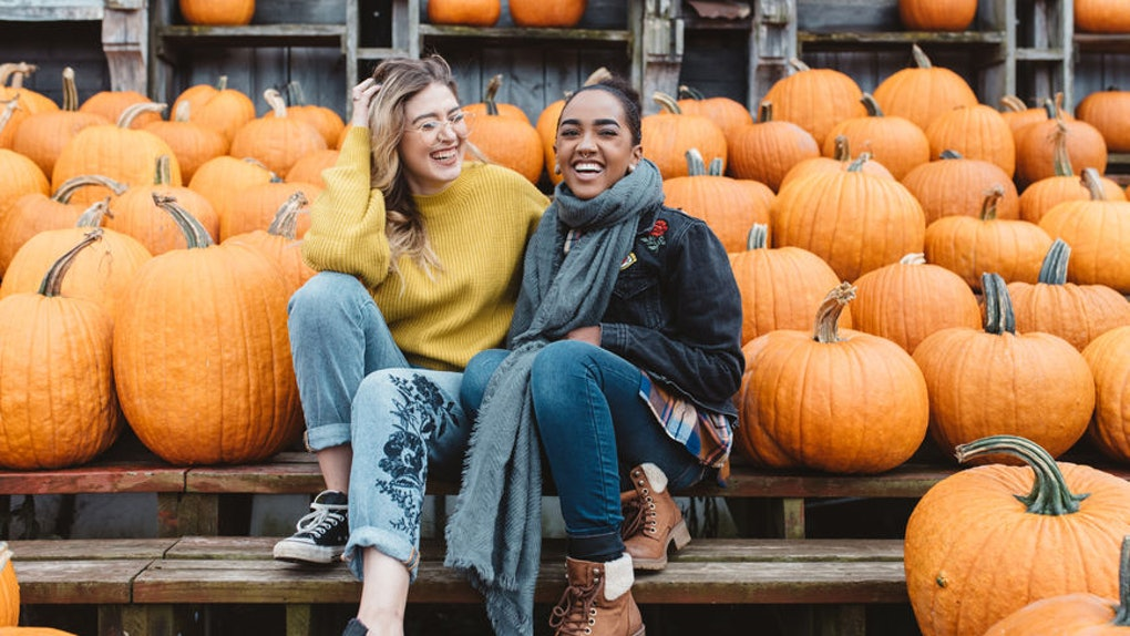 Two girls laughing candidly surrounded by pumpkins is the perfect picture pose to pair with pumpkin quotes for Instagram.
