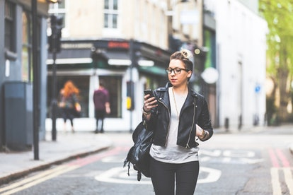 a young woman walking alone looks at her phone