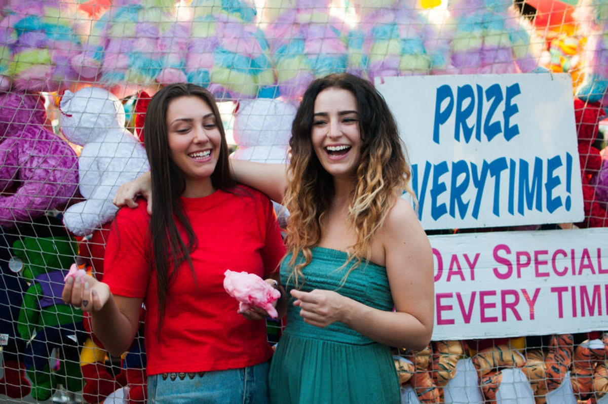 Friends laughing at a fall fair before posting a pic on Instagram with a cute carnival caption.